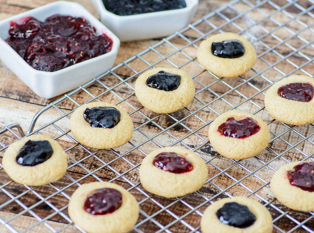 Only 6 ingredients to these melt-in-your-mouth holiday cookies. These Gluten free Jam Thumbprint Cookies are tender, buttery and generously filled with your favorite choice of jam!! Yum!