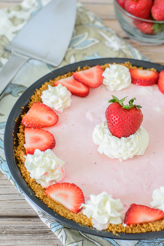 Strawberry Frozen Yogurt Pie! This delicious no bake pie recipe is the perfect frozen summer treat! Great to take to BBQs, picnics or just enjoy as an evening treat. Delicious!